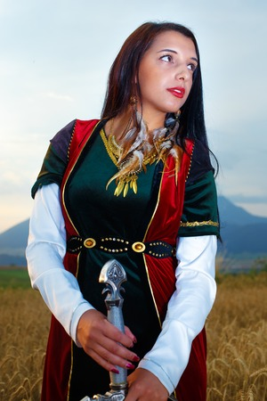 valkyrie: Beautiful  sexy woman warrior with sword.  land background