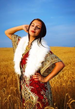 white fur: Young woman with ornamental dress and white fur standing on a wheat field with sunset. Natural background.