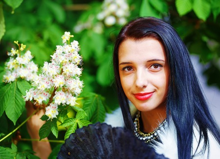 white fur: Beautiful Girl with flowers, glamour white fur, posing next to blooming magical spring  flowers. Flower Background