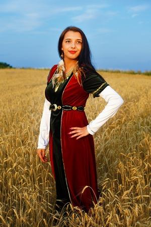 vestido medieval: Sonriente mujer joven con vestido medieval de pie en un campo de trigo con puesta de sol. Fondo natural Foto de archivo