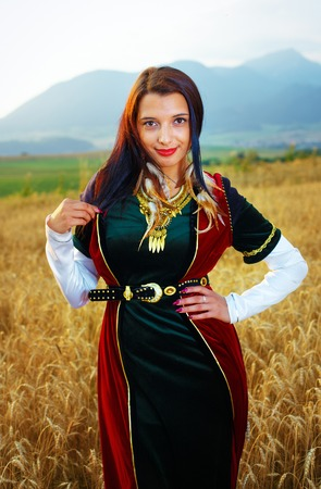 velvet dress: young woman with dark hair, green and red velvet historical dress and gold jewel and a subtle smile.
