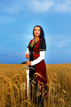 hauberk: Smiling Young woman with ornamental dress and sword in hand  standing on a wheat field with sunset. Natural background.
