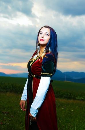 medieval dress: Sonriente mujer joven con vestido medieval con la puesta del sol. Fondo natural