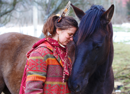 Portrait woman and horse in outdoor. Woman hugging a horse and has feather in her hair.