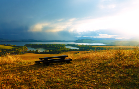 tyan shan mountains: Beautiful landscape. Wooden bench in the meadow, overlooking the lake and mountains with beautiful cloudy sky.