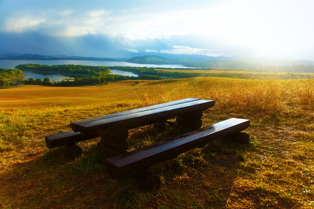 tyan shan: Beautiful landscape. Wooden bench in the meadow, overlooking the lake and mountains with beautiful cloudy sky.