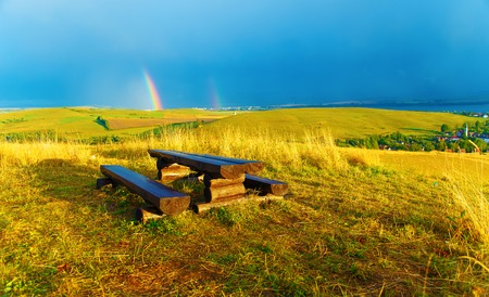 Beautiful landscape. Wooden bench in the meadow, and village