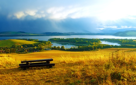 tyan shan mountains: Beautiful landscape. Wooden bench in the meadow, overlooking the lake and mountains  and village with beautiful cloudy sky.