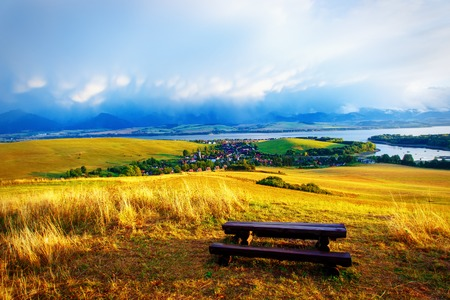tyan shan: Beautiful landscape. Wooden bench in the meadow, overlooking the lake and mountains  and village with beautiful cloudy sky.