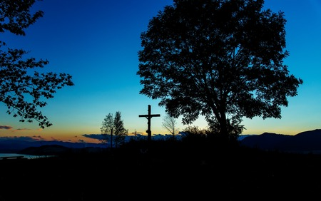 crucify: wooden crosses sit upon a hill in the sunset with tree and lake.