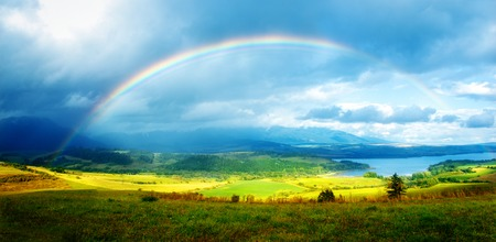 Beautiful landscape, green and yellow meadow and lake with mountain on background with a rainbow in the sky.