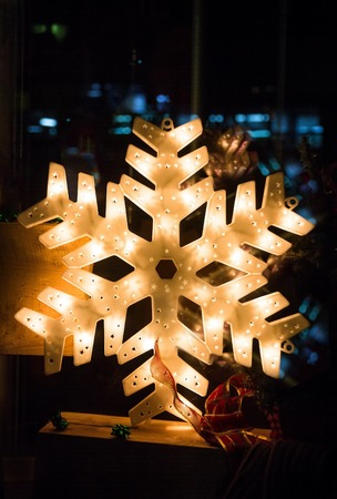nocturnal: Shiny electric christmas snow flake symbol, on dark nocturnal background Stock Photo