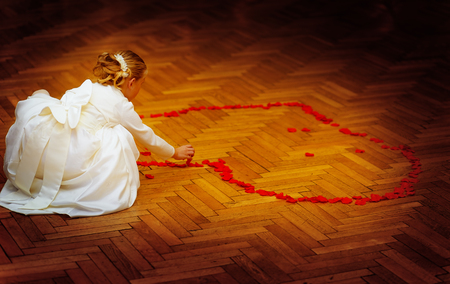 dancefloor: little bridesmaid girl in white dress forming a heart shape out of rose petals.  wedding concept