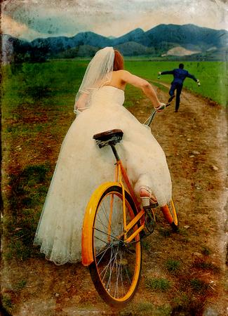 novia en bicicleta retro naranja está persiguiendo después de un novio en traje azul de la boda con una botella de cerveza. concepto de la boda. variante retro