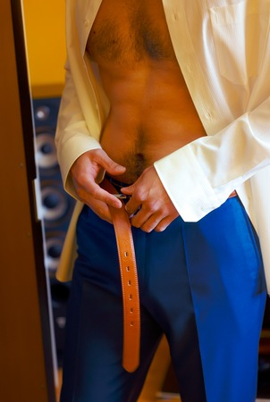 vistiendose: el novio de vestirse ponerse un cintur�n y pantalones de boda Foto de archivo