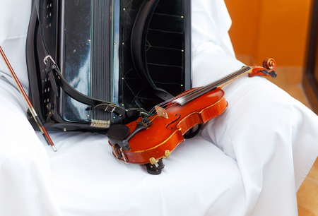 fiddles: wedding stillife with violin and accordeon on a white cloth