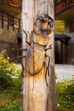 tallado en madera: bug talla de madera sobre fondo de madera, escarabajo de Lucanus Cervus, Escarabajo de macho Foto de archivo