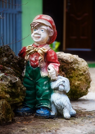 lawn gnome: colorful garden dwarf statue with little puppy Stock Photo