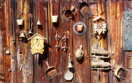 assemblage: antique old style retro object assemblage on a wooden wall. rustic stile. Rake in blueberries, clock, bell, art, old skates and others