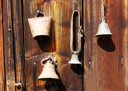 assemblage: antique old style retro object assemblage on a wooden wall. rustic stile. Old shepherds bells Stock Photo