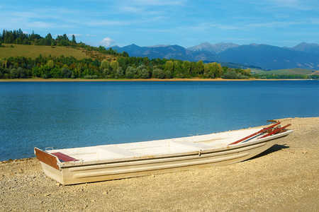 warm water fish: Small old fishing boat on a lake shore