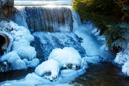 wintrily: Winter scene with water falling from icy rocks Stock Photo