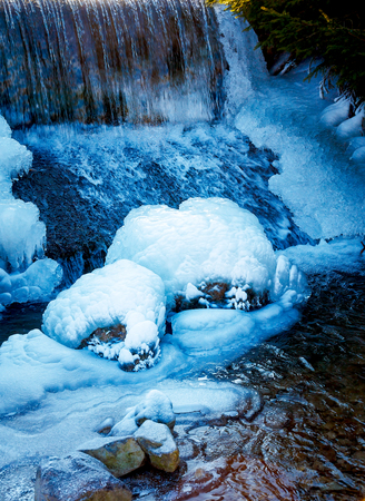 icy: Winter scene with water falling from icy rocks Stock Photo