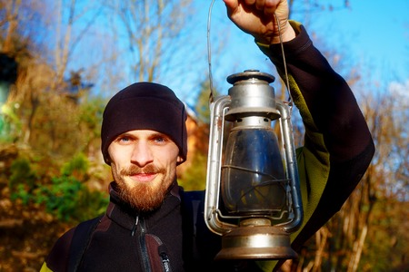 loy: young handsome man in sport outfit holding old lantern. Eye contact