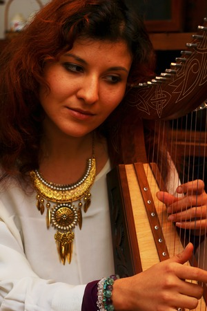 bard: girl harpist in white dress with jewels playing her instrument