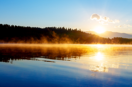 beautiful landscape with mountains and lake at dawn in golden blue and orange tones