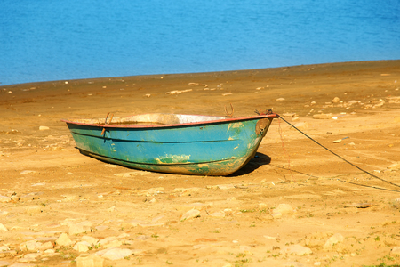 Small old fishing boat on a lake shore