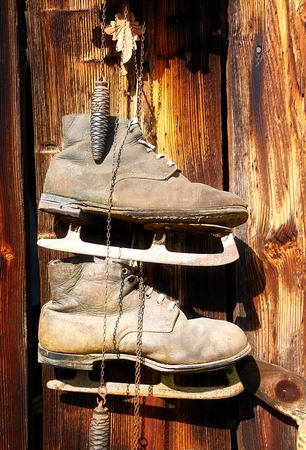 assemblage: antique old style retro object assemblage on a wooden wall, rustic stile. Old skates