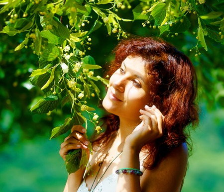 enchantment: gentle prayer to a beautiful linden tree on bright midsummer day Stock Photo