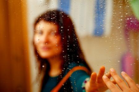 nevelige weerspiegeling van meisje in de spiegel met waterdruppeltjes Stockfoto