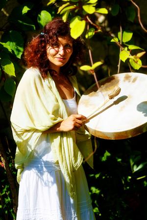 eye catcher: beautiful shamanic girl playing on shaman frame drum in the nature