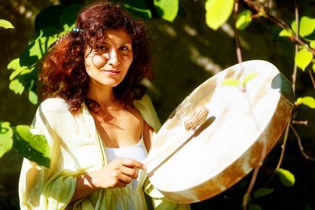 shamanic: beautiful shamanic girl playing on shaman frame drum in the nature