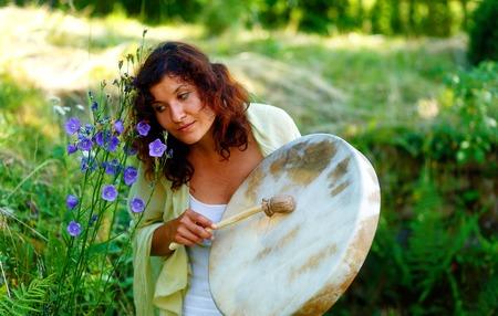 psique: hermosa chica chamánica con tambor de marco chamán en el fondo con hojas y flores