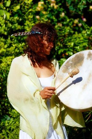 shamanic: beautiful shamanic girl playing on shaman frame drum on background with leaves and flowers