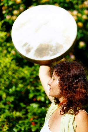 shamanic: girl holding a shamanic frame drum in her hand in the nature