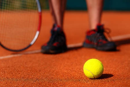 tennis court with tennis ball and man legs on background Stock Photo