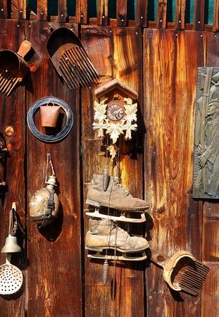 reloj cucu: antigüedad del viejo estilo retro objeto de encaje en una pared de madera. rustica. El rastrillo de arándanos, reloj, campana, arte, viejos patines y otros