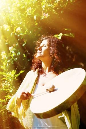 hermosa niña jugando en chamánico tambor de marco chamán en el fondo con hojas y flores. efecto de la luz solar