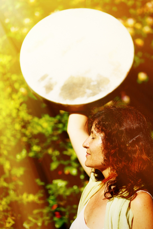 shamanic: girl holding a shamanic frame drum in her hand in the nature. solar light effect