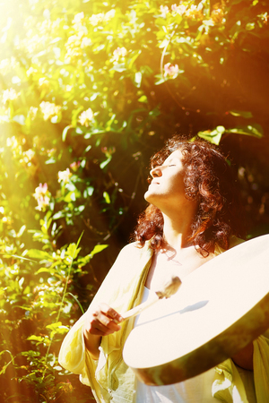 shamanic: beautiful shamanic girl playing on shaman frame drum on background with leaves and flowers. solar light effect