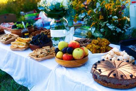wedding feast: Beautiful wedding feast in nature, abundance of meals on a table Stock Photo