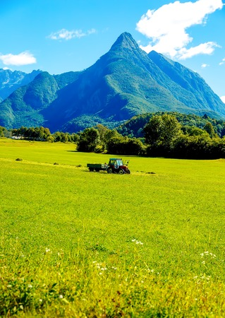 Tractor on green meadow and beautiful Alpine mountains in the background Stock Photo