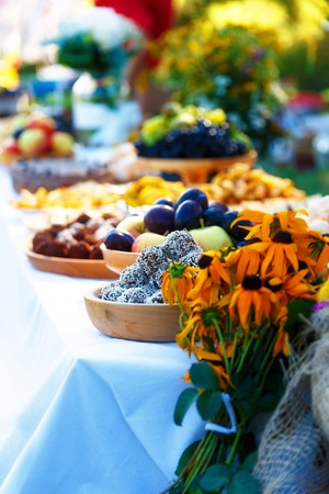 Beautiful wedding feast in nature, abundance of meals on a table Stock Photo
