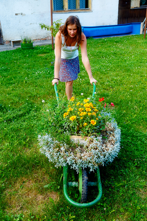 young woman in garden playfully pushing decorative wheelbarrow full of flowers Stock Photo