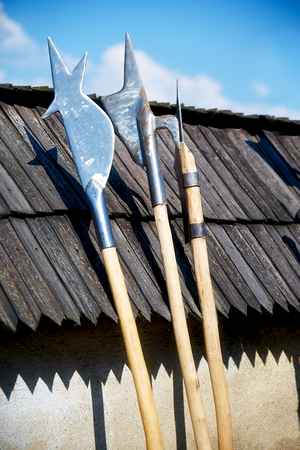 set of middle age style weapons leaning on wooden tiled roof Stock Photo