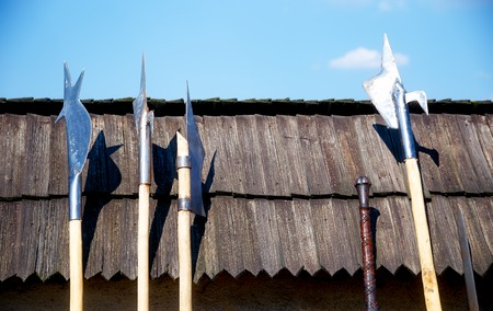 halberd: set of middle age style weapons leaning on wooden tiled roof Stock Photo